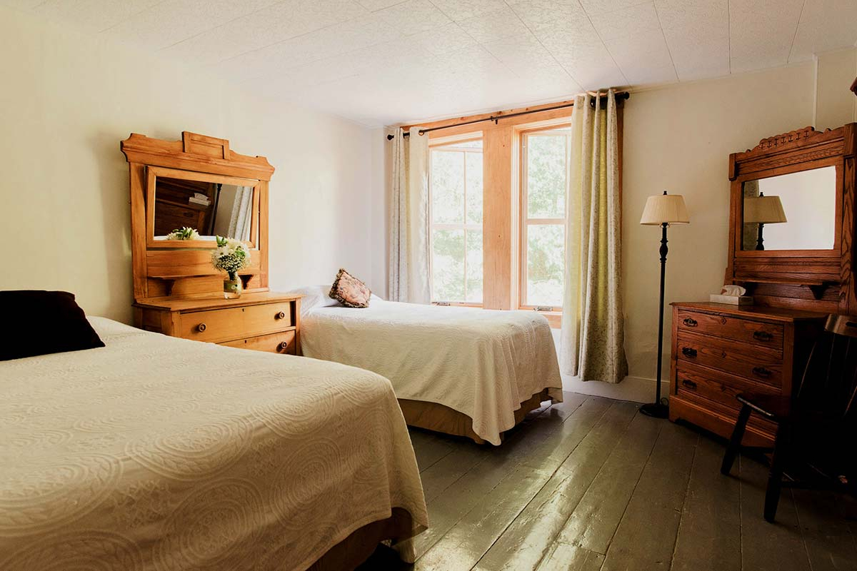 Room 1 - queen and twin beds with view of surrounding forest