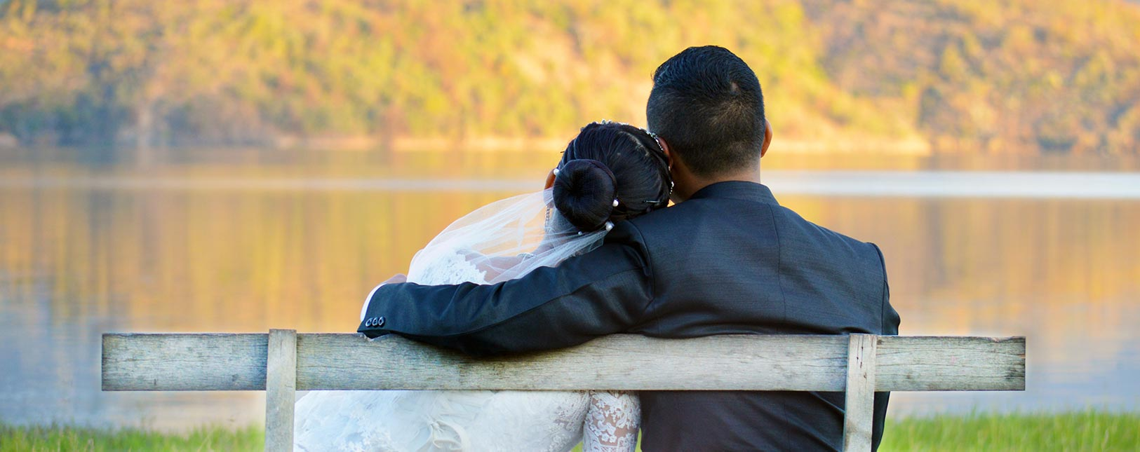 Husband and wife sitting on bench by lake